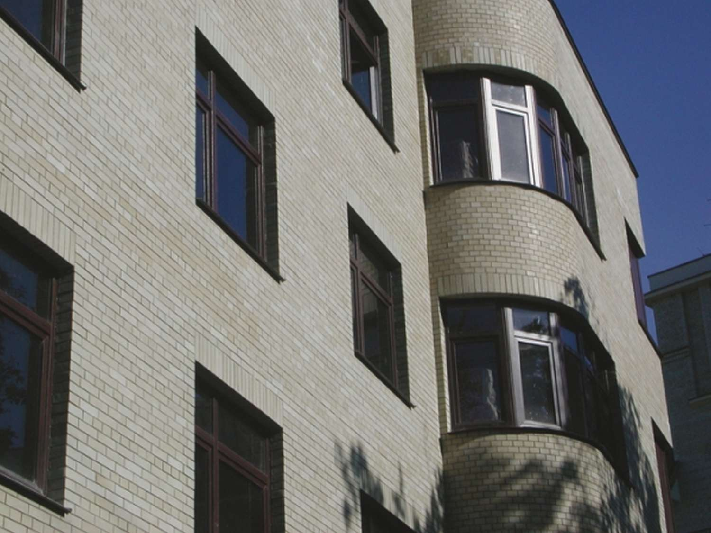 Стена жилого дома отделанная офактуренным кирпичом